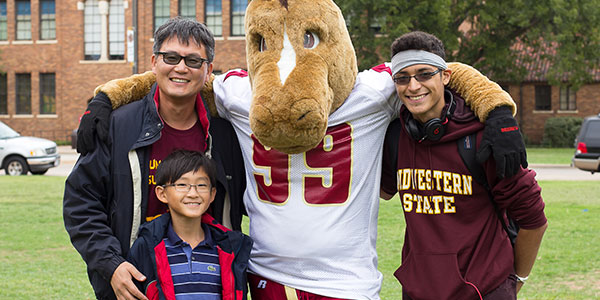 Father and two sons standing together on campus celebrating Family Day event.